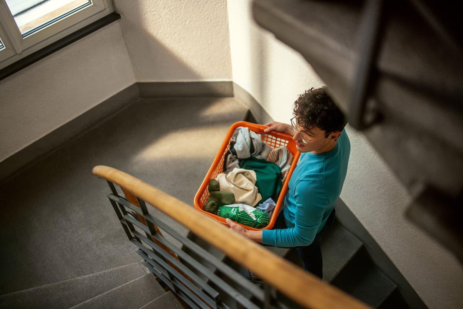 Ein junger Mann mit einen Korb voller Wäsche läuft das Treppenhaus hoch.
