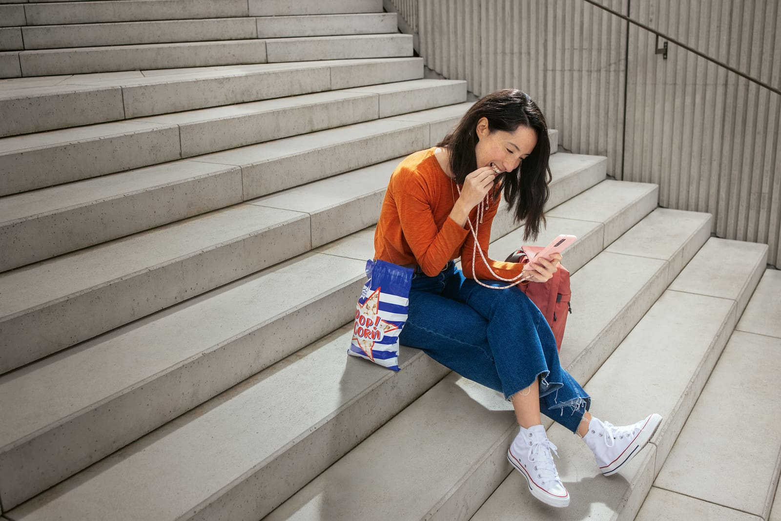 Una ragazza siede su una scala di cemento, mangia popcorn e guarda il suo smartphone.
