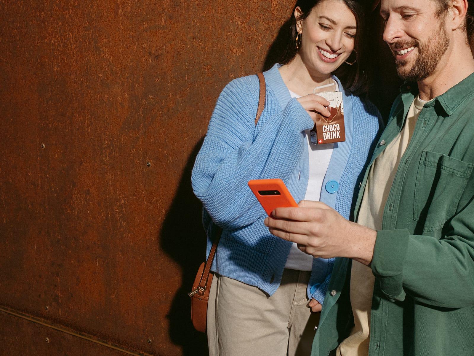 Zwei Personen schauen auf ein Mobiltelefon und schauen sich die Migipedia App an