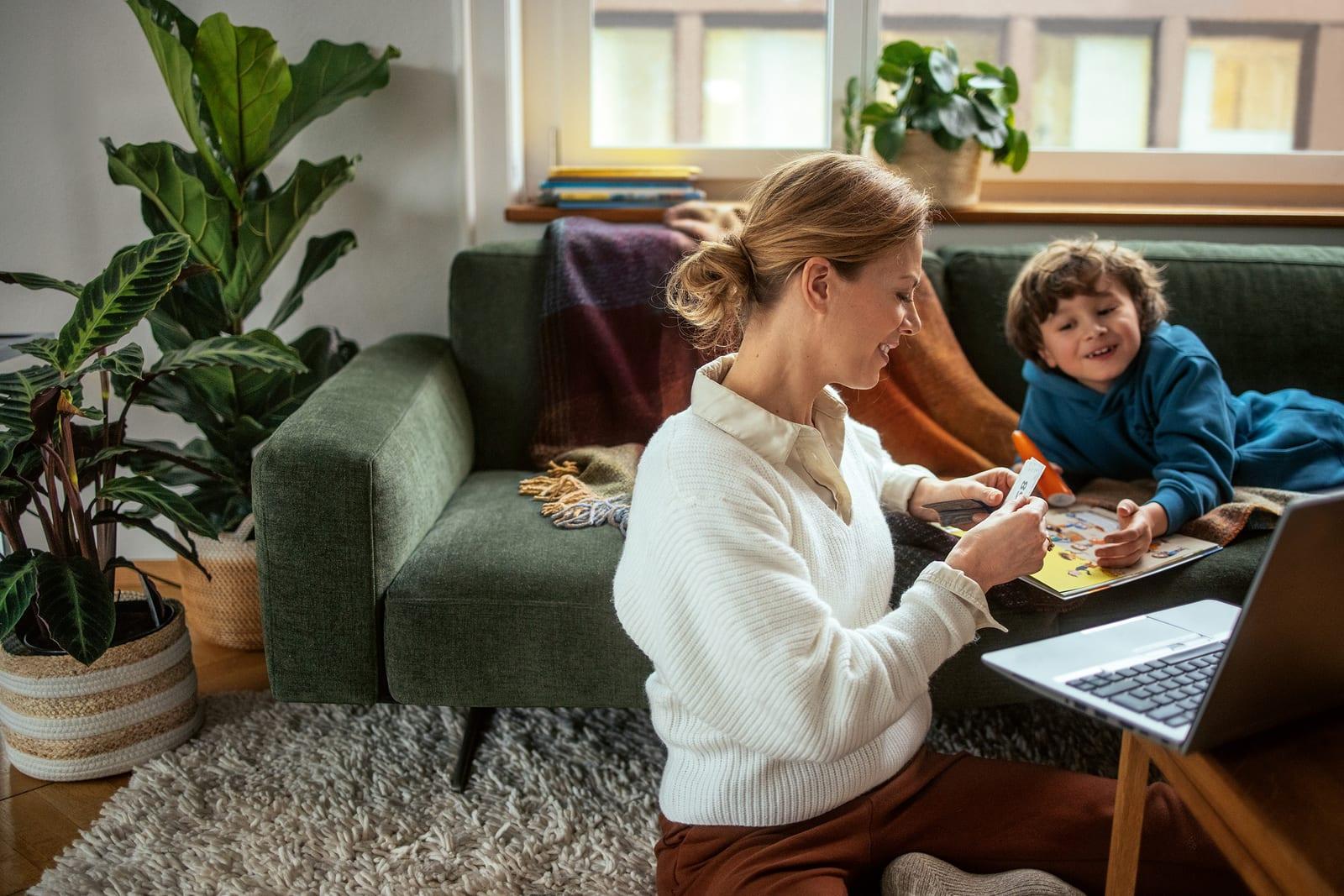 Una persona siede con il proprio figlio in soggiorno. Riordinano elementi della collezione Migros Mania.