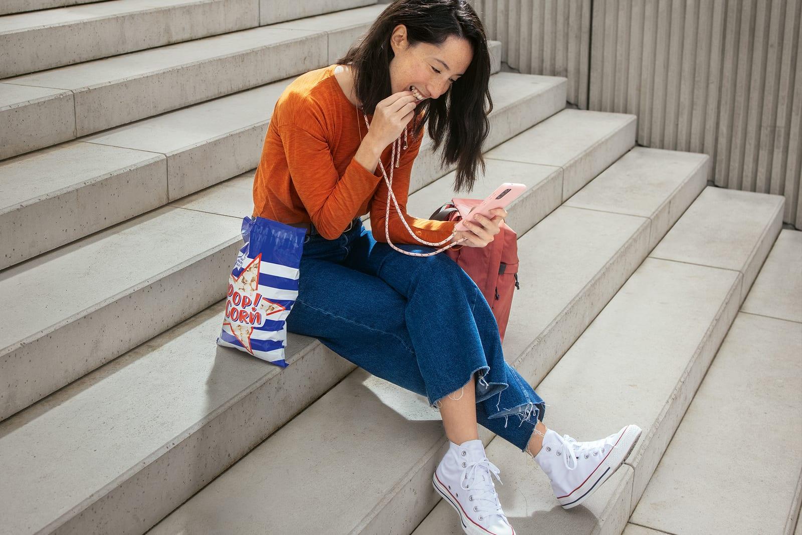 Frau sitzt auf Treppe mit Mobiletelefon in der Hand und isst Popcorn