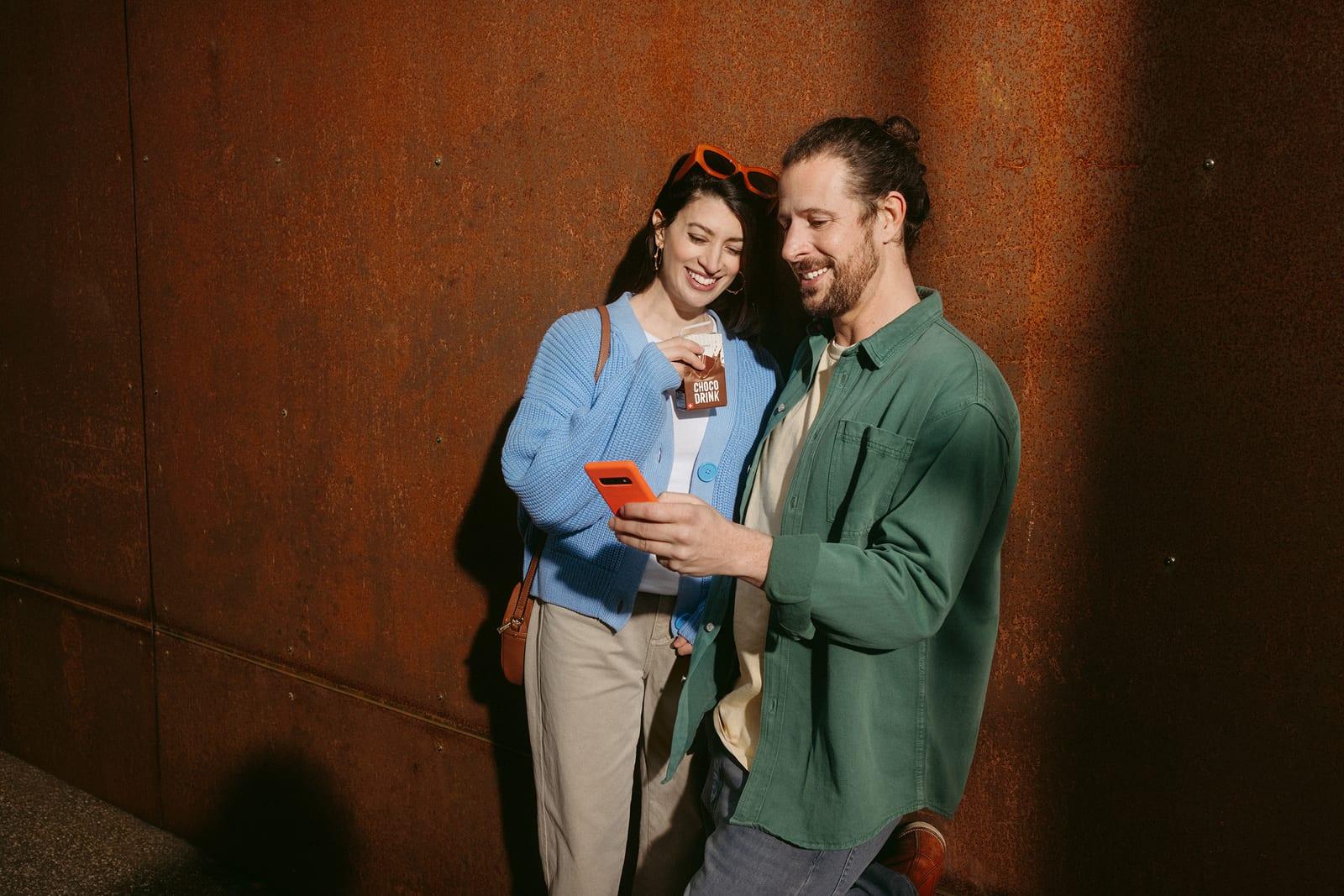 Ein junges Paar steht vor einer Wand. Beide schauen auf das Smartphone, dass er Mann in der Hand hälft und diskutieren.