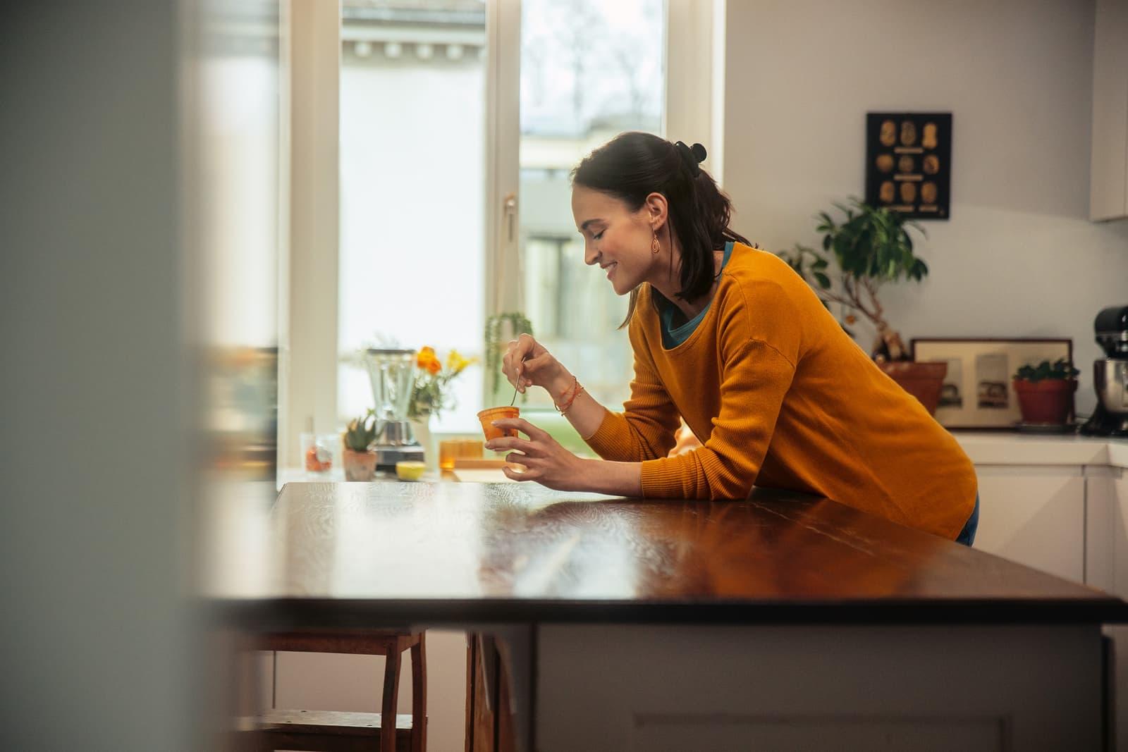 Eine Frau steht in der Küche und leht an den Tisch, während sie ein Joghurt probiert.