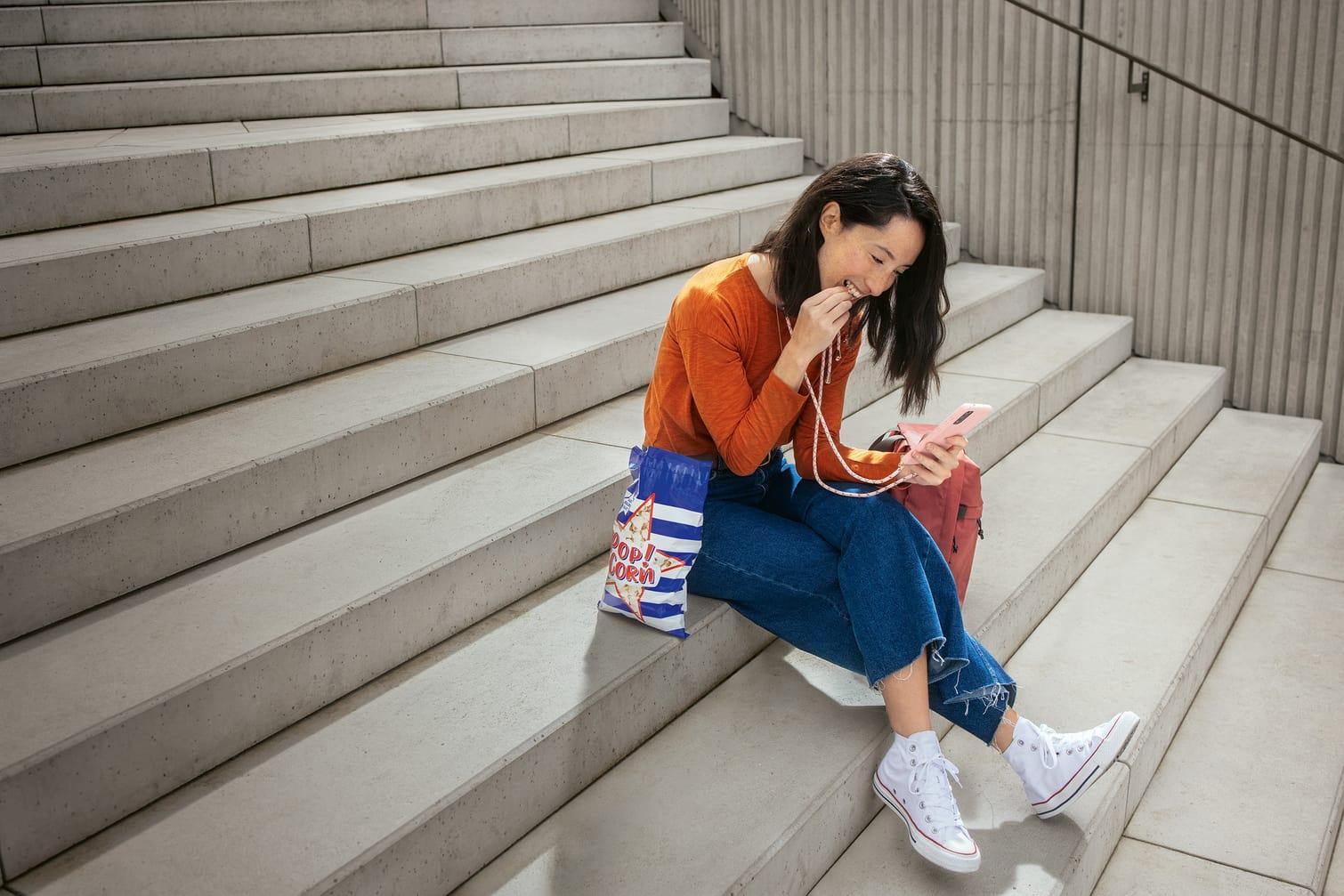 Eine junge Frau sitzt auf einer Beton-Treppe, isst Popcorn und schaut dabei auf ihr Smartphone.