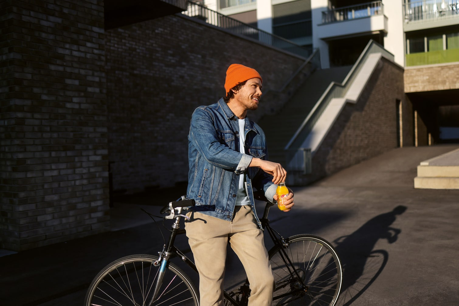 Ein Mann leht an sein Fahrrad an und öffnet einen Orangensaft.